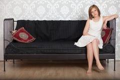 Mujer feliz que se sienta en un sofá Foto de archivo libre de regalías