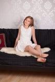 Mujer feliz que se sienta en un sofá Imágenes de archivo libres de regalías