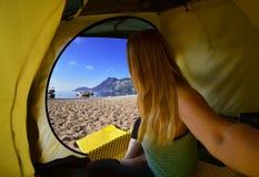 Mujer feliz que se sienta en una tienda, la vista de montañas, el cielo y el mar Imagen de archivo