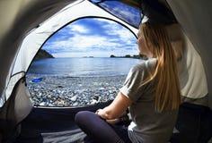 Mujer feliz que se sienta en una tienda, la vista de montañas, el cielo y el mar Foto de archivo libre de regalías