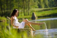 Mujer feliz que se sienta por el lago que salpica el agua Imagen de archivo