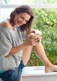 Mujer feliz que se sienta por la ventana que sostiene la taza de café Fotografía de archivo