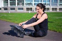 Mujer feliz que se sienta y que pone en patines en línea Imagen de archivo