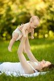 Mujer feliz que se sostiene en el bebé del brazo que miente en hierba Imagen de archivo libre de regalías