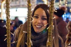 Mujer feliz que siente el ambiente urbano de la Navidad en la noche Mujer feliz que considera para arriba con la luz de la Navida Imagen de archivo libre de regalías