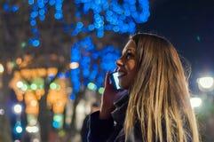 Mujer feliz que siente el ambiente urbano de la Navidad en la noche Mujer feliz que considera para arriba con la luz de la Navida Fotos de archivo