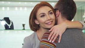 Mujer feliz que sonríe abrazando a su hombre después de hacer compras en la joyería