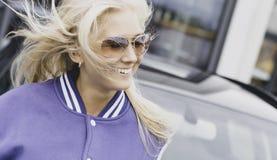 Mujer feliz que sonríe al lado del coche Foto de archivo libre de regalías