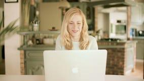 Mujer feliz que sonríe en el ordenador portátil almacen de metraje de vídeo
