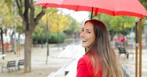 Mujer feliz que sonríe mirando la cámara debajo de la lluvia almacen de metraje de vídeo