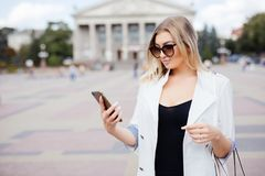 Mujer feliz que sonríe y que camina en la calle usando un smartphone Imagenes de archivo