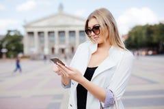 Mujer feliz que sonríe y que camina en la calle usando un smartphone Imagen de archivo