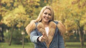 Mujer feliz que sonríe y que muestra los pulgares para arriba en el parque del otoño, seguro social metrajes