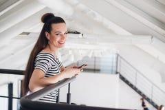 Mujer feliz que sonríe y que se coloca dentro usando un smartphone y que mira la risa de la cámara Imagen de archivo