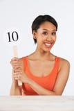 Mujer feliz que soporta la tarjeta de puntuación que da a Mark Out Of Ten Imagenes de archivo