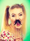 Mujer feliz que sostiene el bigote falso en el palillo Imagen de archivo