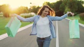 Mujer feliz que sostiene el bolso de compras que camina en la calle en la puesta del sol almacen de metraje de vídeo