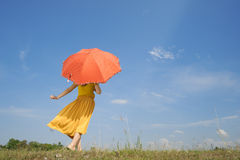 Mujer feliz que sostiene el cielo del paraguas y de la nube imagenes de archivo