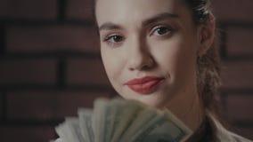 Mujer feliz que sostiene el dinero en las manos que miran a la cámara en fondo de la pared de ladrillo almacen de metraje de vídeo
