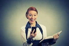 Mujer feliz que sostiene el libro que mira el teléfono que ve buenas noticias Foto de archivo libre de regalías