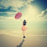 Mujer feliz que sostiene el paraguas y que salta en cielo del sol del mar Imagen de archivo