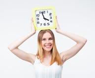 Mujer feliz que sostiene el reloj grande en la cabeza Imágenes de archivo libres de regalías