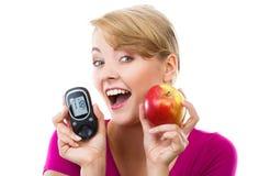 Mujer feliz que sostiene glucometer y la manzana fresca, midiendo y comprobando el nivel del azúcar, concepto de diabetes Imagen de archivo libre de regalías