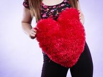 Mujer feliz que sostiene la almohada en forma de corazón Fotografía de archivo