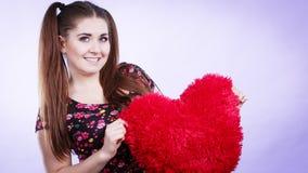 Mujer feliz que sostiene la almohada en forma de corazón Imagen de archivo