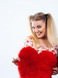 Mujer feliz que sostiene la almohada en forma de corazón Foto de archivo