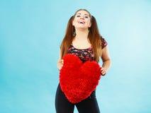 Mujer feliz que sostiene la almohada en forma de corazón Fotos de archivo libres de regalías