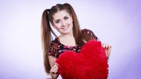 Mujer feliz que sostiene la almohada en forma de corazón Imágenes de archivo libres de regalías