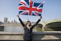 Mujer feliz que sostiene la bandera británica mientras que se opone a Big Ben en Londres, Inglaterra, Reino Unido Fotos de archivo libres de regalías