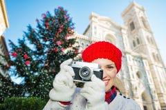 Mujer feliz que sostiene la cámara de la foto cerca del árbol de navidad en Florencia Fotos de archivo