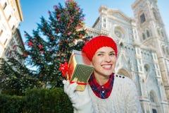 Mujer feliz que sostiene la caja de regalo cerca del árbol de navidad en Florencia Foto de archivo