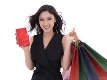 Mujer feliz que sostiene la caja y el panier de regalo aislados en una pizca imagen de archivo libre de regalías