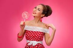 Mujer feliz que sostiene la piruleta roja Pin-Para arriba retro Imagen de archivo libre de regalías
