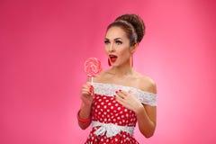 Mujer feliz que sostiene la piruleta roja Pin-Para arriba retro Foto de archivo