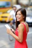 Mujer feliz que sostiene la tableta de Digitaces en la calle de la ciudad Foto de archivo