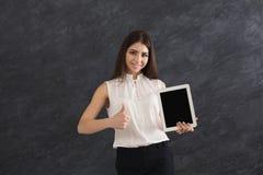 Mujer feliz que sostiene la tableta digital en fondo gris Imagen de archivo