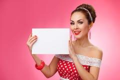Mujer feliz que sostiene la tarjeta en blanco Pin-Para arriba retro Imagen de archivo