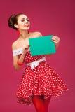 Mujer feliz que sostiene la tarjeta en blanco Pin-Para arriba retro Foto de archivo