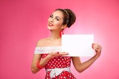 Mujer feliz que sostiene la tarjeta en blanco Pin-Para arriba retro Fotos de archivo