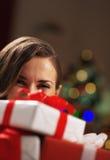Mujer feliz que sostiene las cajas del regalo de Navidad delante de la cara Imagen de archivo libre de regalías