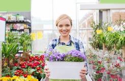 Mujer feliz que sostiene las flores en invernadero Fotografía de archivo