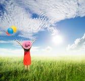 Mujer feliz que sostiene los globos en campos de hierba verde con las nubes Imágenes de archivo libres de regalías