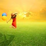 Mujer feliz que sostiene los globos y que salta en campo y los soles de hierba Imagen de archivo