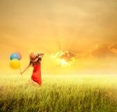 Mujer feliz que sostiene los globos y que salta en campo y los soles de hierba Fotos de archivo