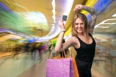 Mujer feliz que sostiene los panieres y la tarjeta de crédito Fotos de archivo libres de regalías
