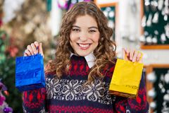 Mujer feliz que sostiene los pequeños panieres en tienda Foto de archivo libre de regalías
